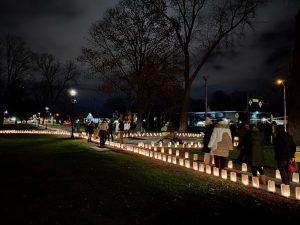 Guests walk along a candlelit path at the luminaria